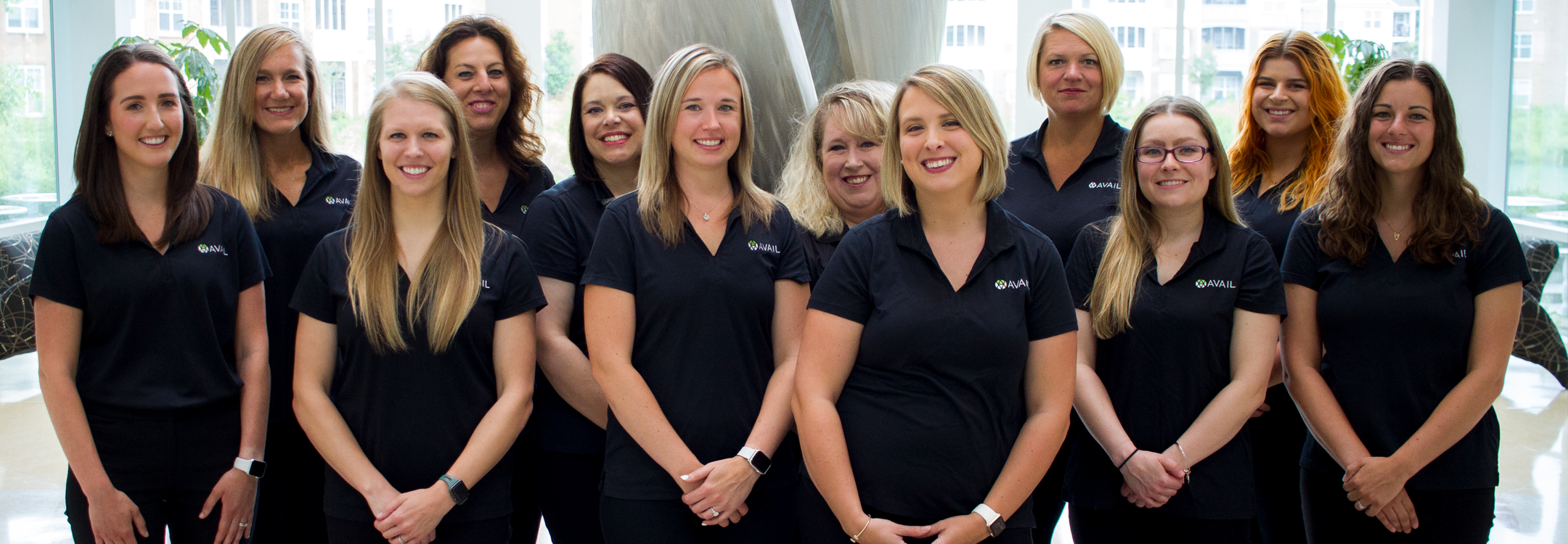 12 female employees wearing AVAIL polos and smiling
